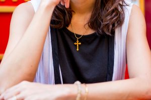 Christian believer praying to God with Cross rosary in her Neck. Focus on Cross.